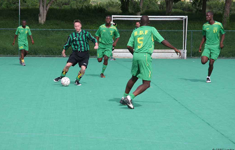 Footballers playing on an artificial surface, with one person about to pass the ball