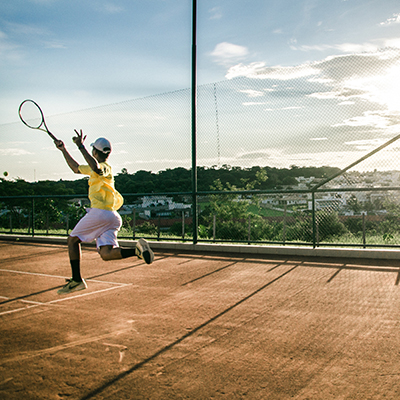 Tennis player hitting an overhead volley on a red court in the sun