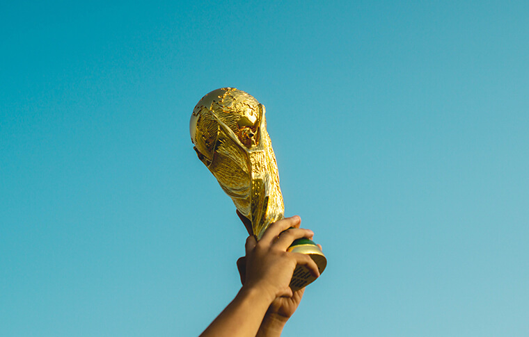 Person holding a gold trophy with 2 hands in the air